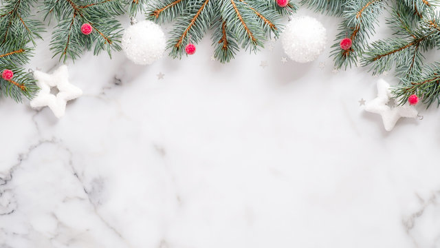 Christmas or New year banner. Pine tree branches, red berry, white balls on marble background top virew. Christmas, New Year, winter holidays concept. Xmas frame