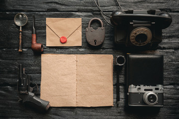 Open blank page detective book with various equipment around on black wooden table background.