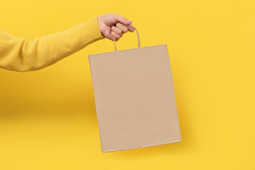 Woman hand holding paper shopping bag on yellow background. Shopping concept.