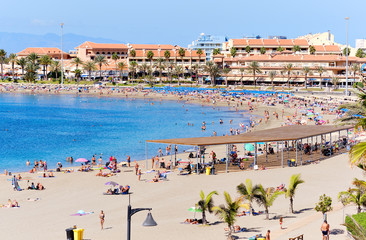 People sunbathing on sandy beach of Playa de los Cristianos, enjoy warm Atlantic Ocean waters, townscape and hotels exterior, Tenerife, Canary Islands, Spain