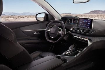 Cockpit of a modern SUV with a view of the desert and mountains. In the mirror you can see the road on which it stands.