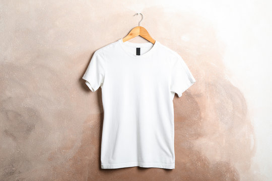 Hanger with blank white t-shirt on brown background, space for text