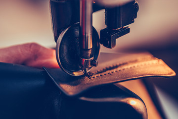 Shoemaker hands stitching a part of the shoe  in the handmade footwear industry