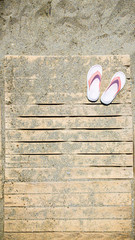 Top view shot of white and pink flip flops on the wooden flooring of Mediterranean sandy beach in sunny Turkey.