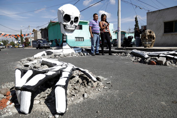 A couple poses for a picture with a giant skeleton rising from the ground, which is a part of an installation to celebrate the Day of the Dead, at Tlahuac borough in Mexico City