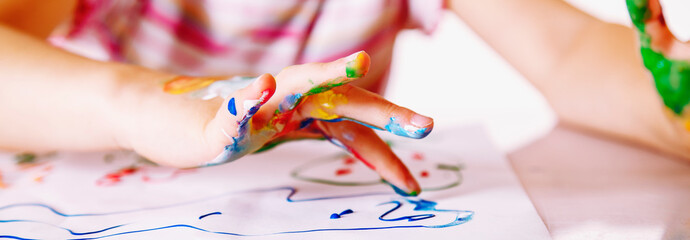 Close up young girl painting with colorful hands. Art,  creativity and painting concept. Horizontal image.