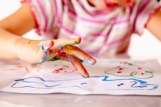 Young girl painting with colorful hands. Art,  creativity and painting concept.