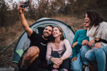Young friends laughing, taking selfie,hanging out at campsite Wall mural