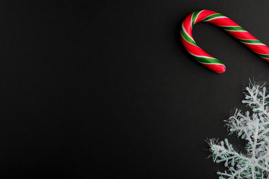 Traditional christmas caramel candy cane and snowflakes on a black background. Winter Holiday festive greeting card with copy space for the text. Xmas flat lay concept.