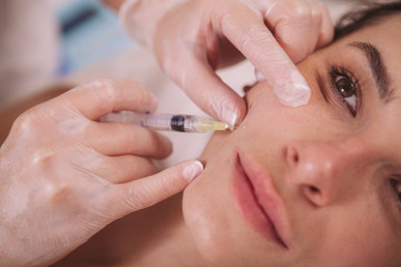 Cropped close up of a beautiful woman getting filler injections in her face. Young woman receiving hyaluronic acid injections by cosmetologist