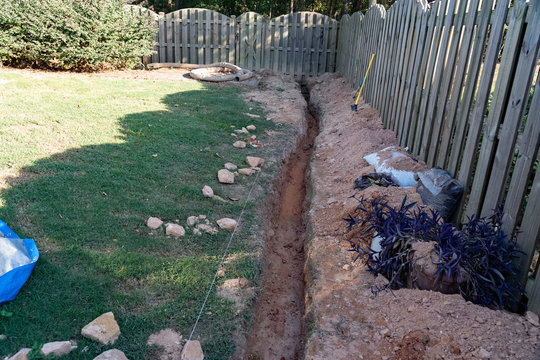 A trench is dug as the first step of a DIY French drain home improvement project to alleviate drainage issues.