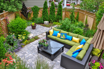 A beautiful small, urban backyard garden featuring a tumbled paver patio, flagstone stepping stones, and a variety of trees, shrubs and perennials add colour and year round interest.