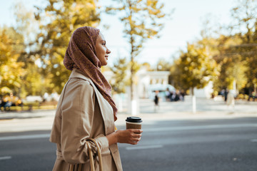 muslim woman on a city street with coffee in hand