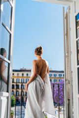girl standing with her back to the camera at the open window