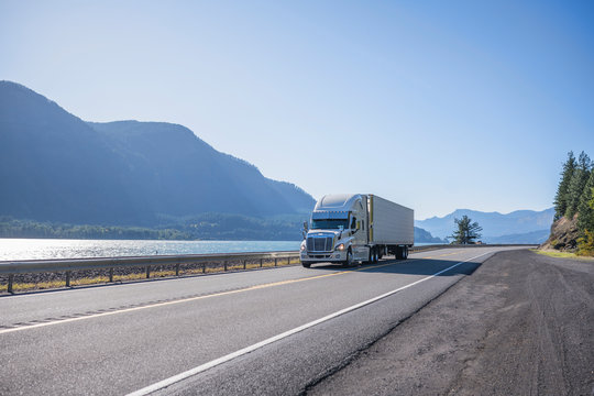 Big rig professional popular semi truck tor long haul freight transporting cargo in refrigerator semi trailer running on the road along the Columbia River at sunny day