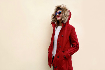 Side view of stylish smiling woman in red jacket with fur hood standing and looking away at blank copy space on wall background