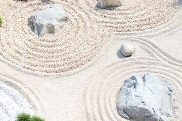 Poster Stones in Sand Zen garden pattern on sand and stone. Top view. Meditation and harmony.