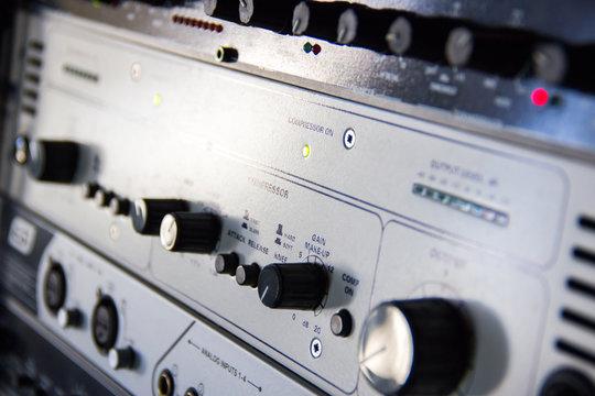 A rack of audio compressors in a recording studio.