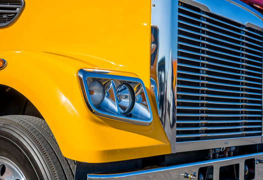 Part of yellow big rig semi truck with chrome grille and headlight with reflection of sunlight