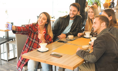 Friends hanging out at a bar and taking selfie- Young people drinking coffee together and using smartphone