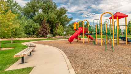Panorama frame Scenic view at a park with colorful childrens playground and benches on pathway