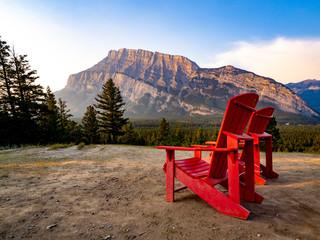 Papiers peints Cappuccino chaises rouges devant une montagne au lever de soleil