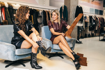 Beautiful young women trying leather boots in expensive boutique or store.. Wall mural