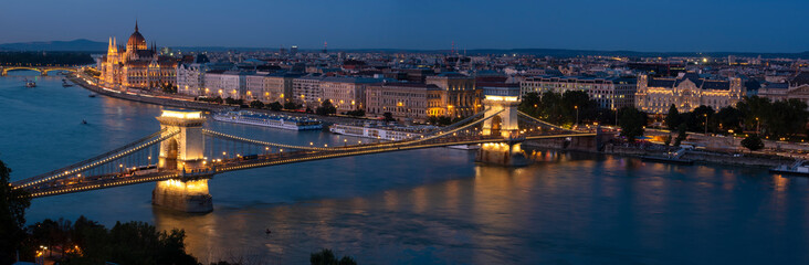 Panorama of Budapest along the Danube River featuring the Chain Bridge and Hungarian Parliament Building at blue hour.  Fototapete