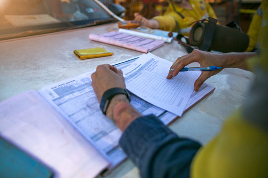 Construction coal miner supervisor conducting safety checking on job hazards analysis on hot work permit before sign off approval to work on  open field construction coal mine site Sydney, Australia