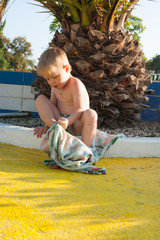 A fair-haired white baby of three years in panties sits on a curb against the background of a palm tree in a water park and wipes his legs with a towel