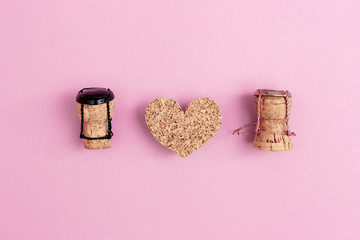 Girl and boy characters from champagne corks and muselets with heart on pink colored background. Concept for Valentines Day or wedding on topic of relations between man and woman. Flat lay.