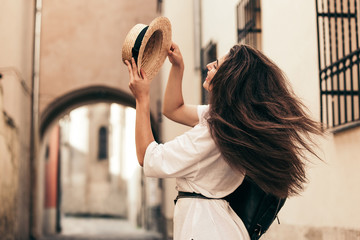 Young stylish woman walking on the old town street, travel with backpack, straw hat, wearing trendy outfit. Wall mural