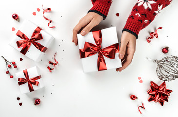 Fototapete - Female hands holding Christmas gift box on white background with fir branches, red decoration, sparkles and confetti. Xmas and New Year greeting card, winter holiday. Flat lay, top view