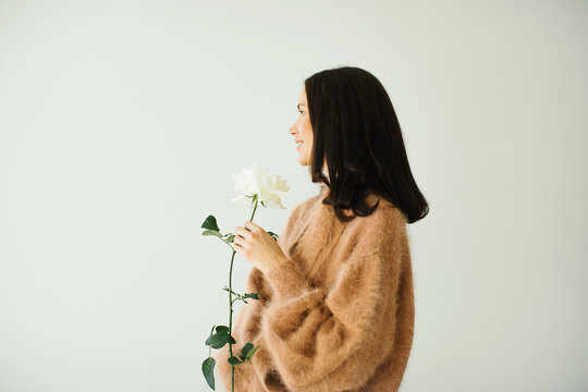 Smiling pretty woman wearing cashmere beige sweater holding a white rose