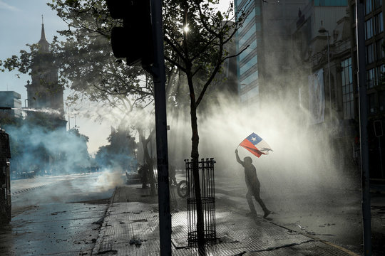 A demonstrator waves a Chilean flag as a riot police vehicle uses a water cannon during a protest against Chile's government in Santiago, Chile