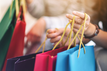 Closeup image of people holding shopping bags together