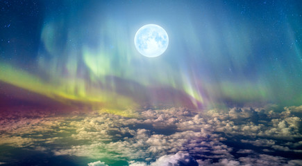 """Northern lights (Aurora borealis) in the sky over clouds with full moon """"Elements of this image furnished by NASA"""""""