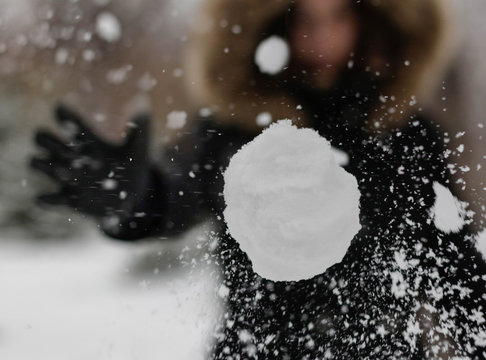 The girl throws a snowball at the camera. The snowball shatters into snowflakes