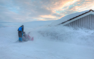 Man working with a snow blowing machine -  A man cleans snow from sidewalks