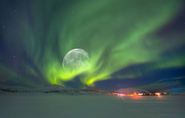 Northern lights (Aurora borealis) in the sky over Tromso with full moon, Norway