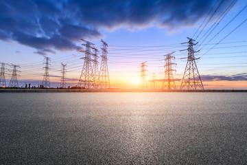 Empty asphalt road and high voltage electricity tower landscape at sunset.