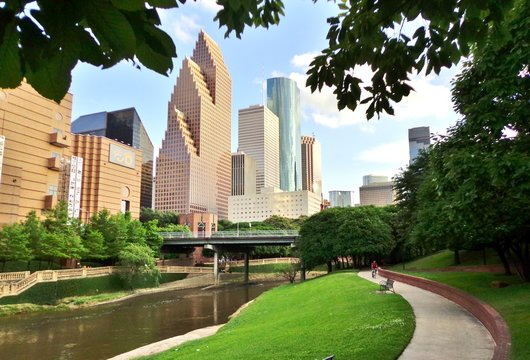 Bicyclist on Paved Bike Path in Buffalo Bayou Park, with the Skyline of Downtown Houston in the Background - Houston, Texas, USA