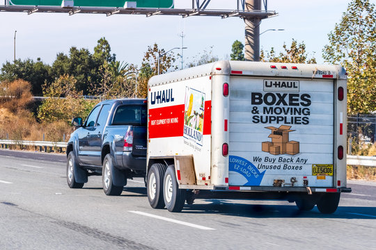 Oct 26, 2019 Mountain View / CA / USA - Semi truck towing an U-Haul cargo trailer, on a freeway in San Francisco bay area; U-Haul is an American moving equipment and storage rental company