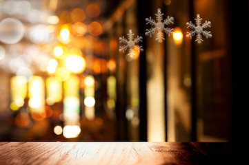 top of black wood table with Christmas snowflake symbol in light of pub or bar party dark night background