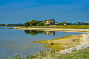 Rutland Water a large reservoir in Leicestershire in the summer with ruins in the distance.