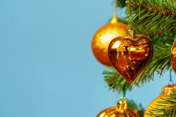 Christmas tree with golden baubles close up on blue background