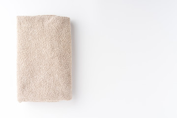 Folded beige towel isolated on white background with copyspace. Top view