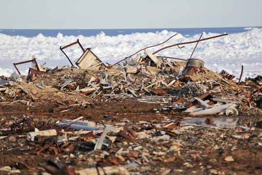 Fuel drums and piles of scrap metal waste in the Arctic