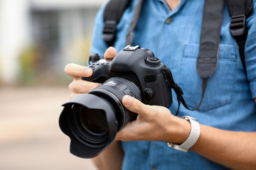 Young male photographer with camera outdoors, closeup