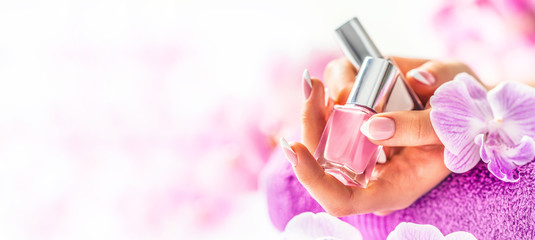 In de dag Manicure Trendy nail manicure. Woman hands holding nails polishes. Pink decoration from orchids